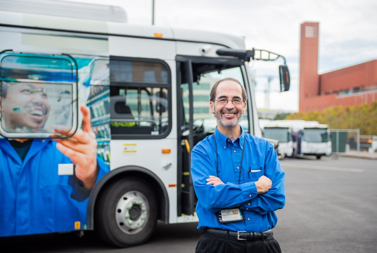 Jose Suarez standing next to one of UCSF's new electric buses.