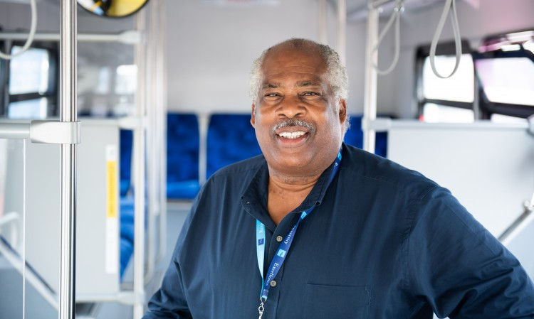 UCSF Driver Steve Dozier standing inside a new electric bus.