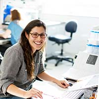 Image of female with glasses, sitting at a desk smiling, in front of computer