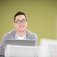 Image of asian male in glasses, smiling, sitting in front of a laptop