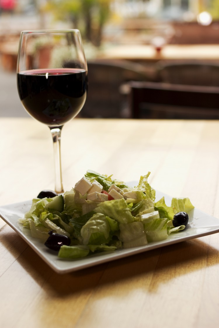 A glass of wine and salad