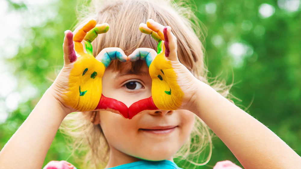 Child making heart with hands