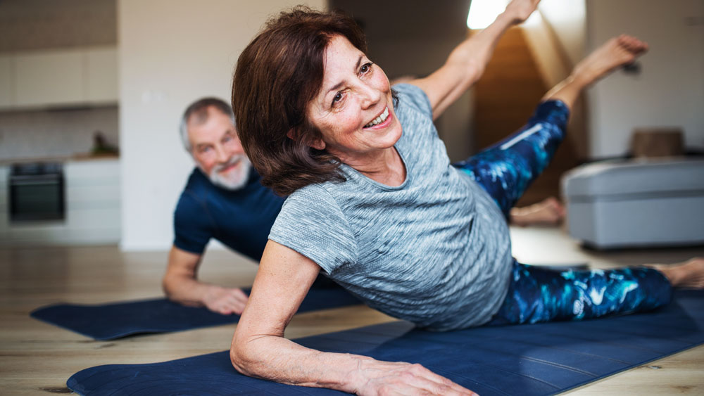 woman and man exercising on mat.