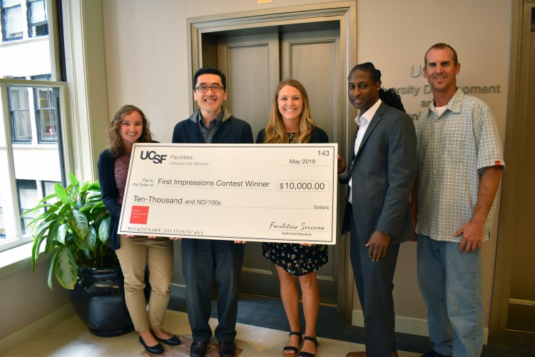 UCSF employees hold big check to celebrate improvements to Irving Street space.