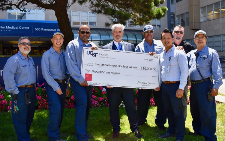 Landscaping employees pose with big check.