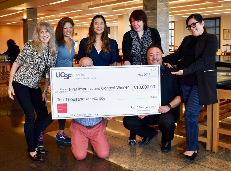 Library staff pose with large check.