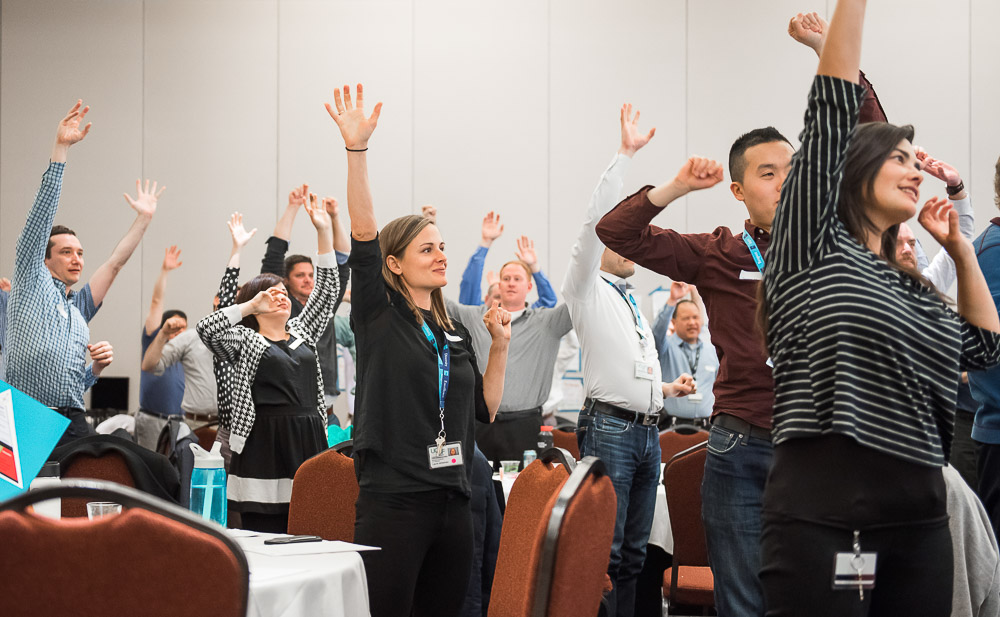 foto of staff stretching around conference tables at 2018 Retreat