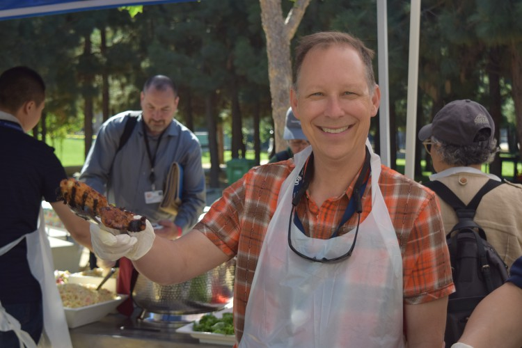 Kevin Cox serves a hamburger at the CLS picnic.